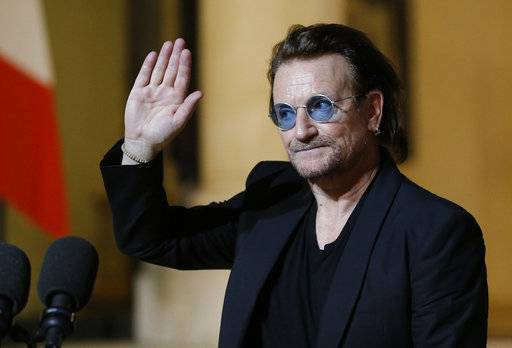 FILE - In this Monday, Sept. 10, 2018, file photo, U2 singer Bono waves goodbye to the media after a meeting with French President Emmanuel Macron at the Elysee Palace in Paris, France. Bono is scheduled to speak in Chicago, Thursday, Dec. 6, 2018, about his efforts to combat AIDS and extreme poverty in Africa.