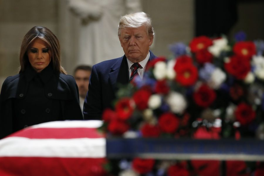 President Donald Trump and first lady Melania Trump pay their respects to former President George H. W. Bush, as he lies in state in the Rotunda of the U.S. Capitol, Monday, Dec. 3, 2018, in Washington.