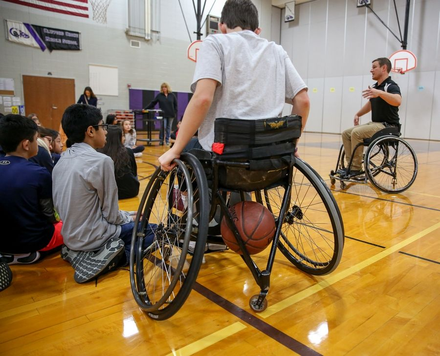 Jason Stubbeman, explains the fundamentals of wheelchair basketball to sixth-grade students at Crone Middle School in Naperville. Student Drew Beutel, center, plays on a wheelchair basketball team.