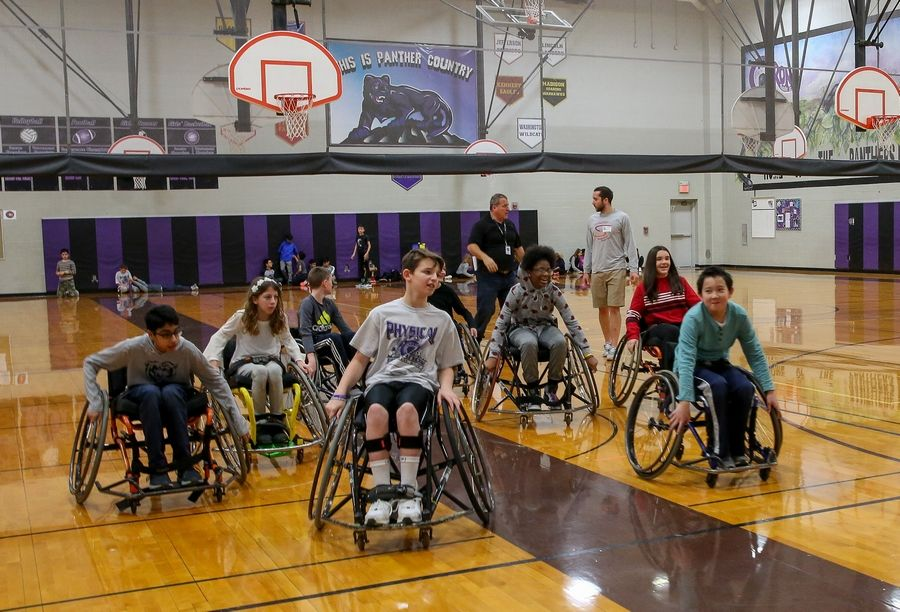 Drew Beutel, center, plays wheelchair basketball Monday with his sixth-grade classmates at Crone Middle School in Naperville.