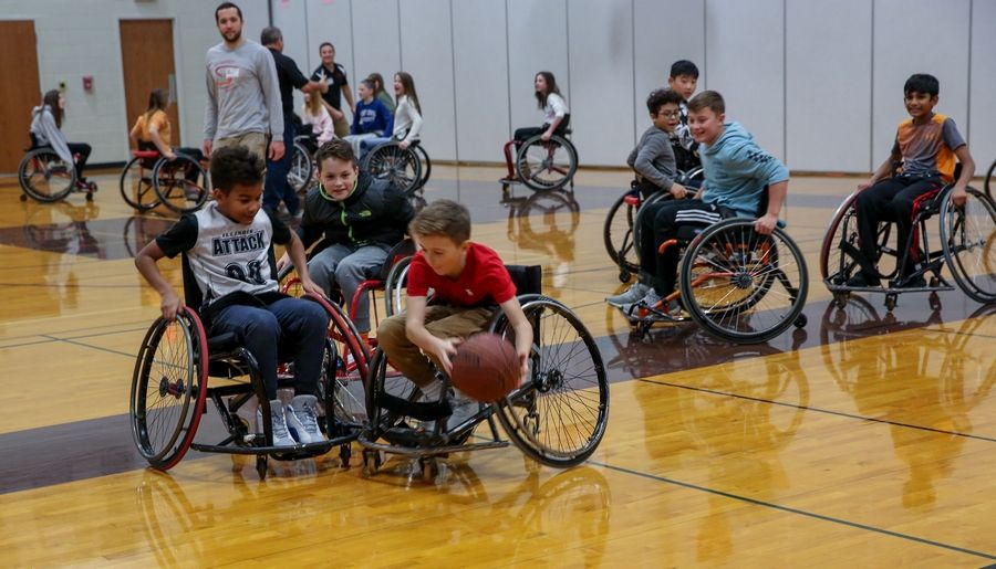 Sixth-grader students give wheelchair basketball a try Monday at Crone Middle School in Naperville.