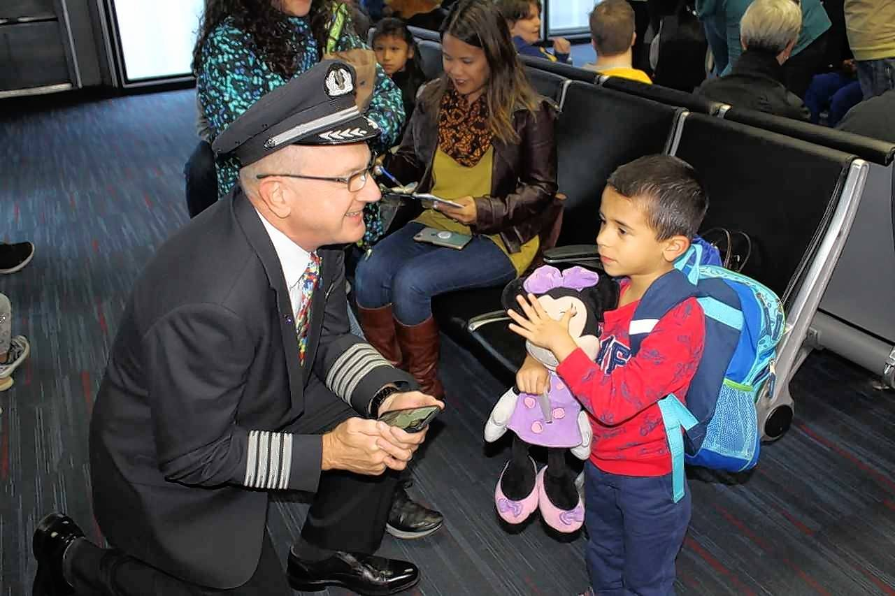 Families with special-needs children recently took part in a mock flight with American Airlines to help them become comfortable with air travel. Aiden Ziemba of Schaumburg, right, visits with American Airlines pilot Kirk Holte.before the flight