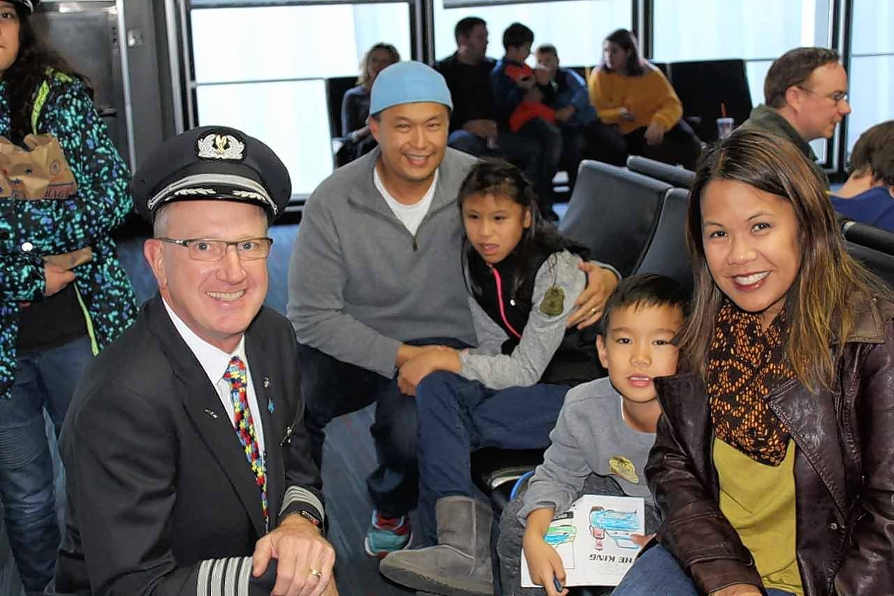 Families with special-needs children recently took part in a mock flight with American Airlines to help them become comfortable with air travel. Cheryl Quijano, right, and her family visit with American Airlines pilot Kirk Holte.