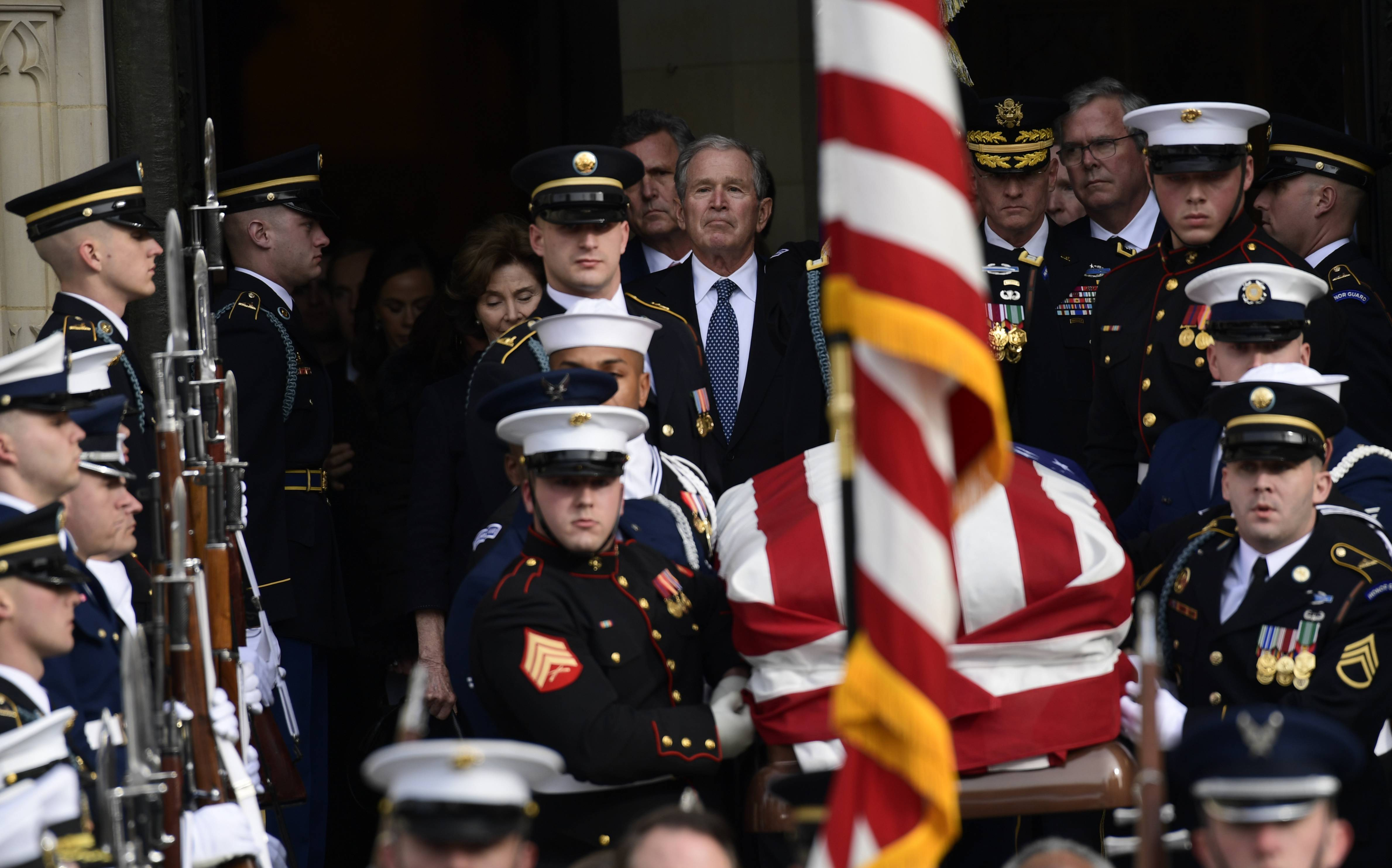 Former President George W. Bush, center, and his wife, Laura Bush, watch Wednesday as the casket of former President George H.W. Bush is carried out after a State Funeral at the National Cathedral in Washington.