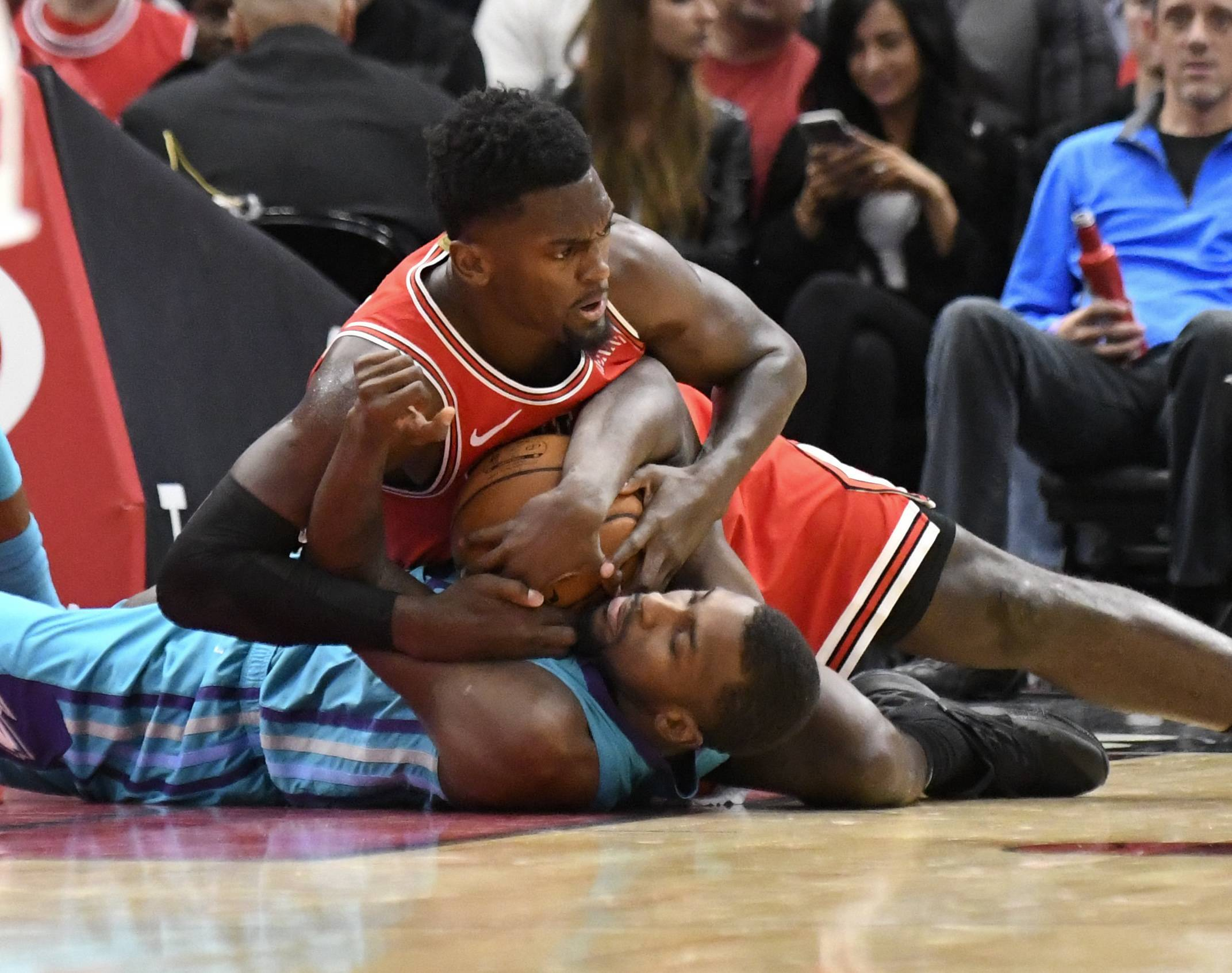Chicago Bulls forward Bobby Portis, top, and Charlotte Hornets forward Michael Kidd-Gilchrist, bottom, fight for the ball during the second half of a NBA basketball game Wednesday, Oct. 24, 2018, in Chicago. The Bulls won 112-110.