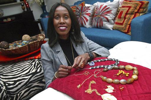 In this Monday, Dec. 3, 2018, photo, Shamila Nduriri, who owns Dalasini, an upscale jewelry company, poses in her Minneapolis apartment with some of her jewelry. Nduriri, who studied finance in college, saved aggressively when she worked for a corporation and continues to put money aside now that she owns Dalasini.