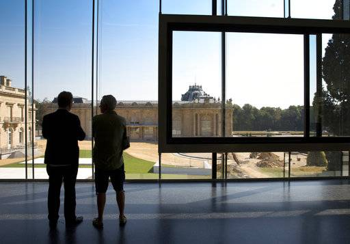 Museum director Guido Gryseels, left, looks out from the new visitor center onto the original Africa Museum in Tervuren, Belgium, Friday, Aug. 3, 2018. The museum is reopening on Saturday Dec. 8, 2018, after more than 10 years spent revamping the building and overhauling its dated, one-sided approach to history.