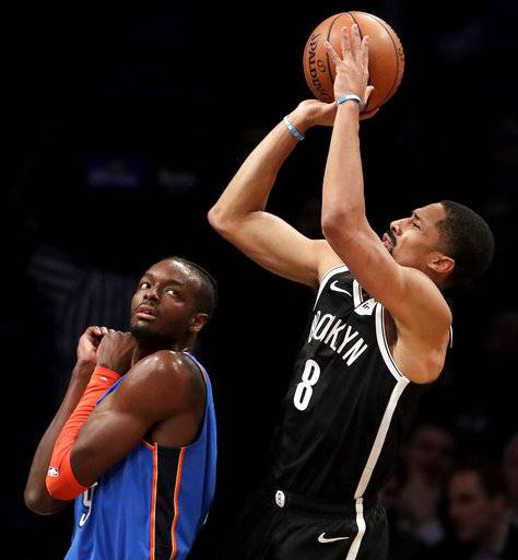 Brooklyn Nets guard Spencer Dinwiddie, right, goes up for a shot against Oklahoma City Thunder forward Jerami Grant during the first half of an NBA basketball game, Wednesday, Dec. 5, 2018, in New York.