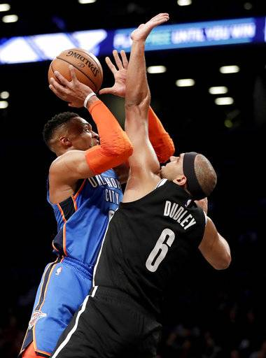 Oklahoma City Thunder guard Russell Westbrook, left, goes up for a shot against Brooklyn Nets forward Jared Dudley during the first half of an NBA basketball game, Wednesday, Dec. 5, 2018, in New York.
