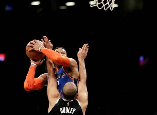 Oklahoma City Thunder guard Russell Westbrook, back, goes up for a shot against Brooklyn Nets forward Jared Dudley during the first half of an NBA basketball game, Wednesday, Dec. 5, 2018, in New York.