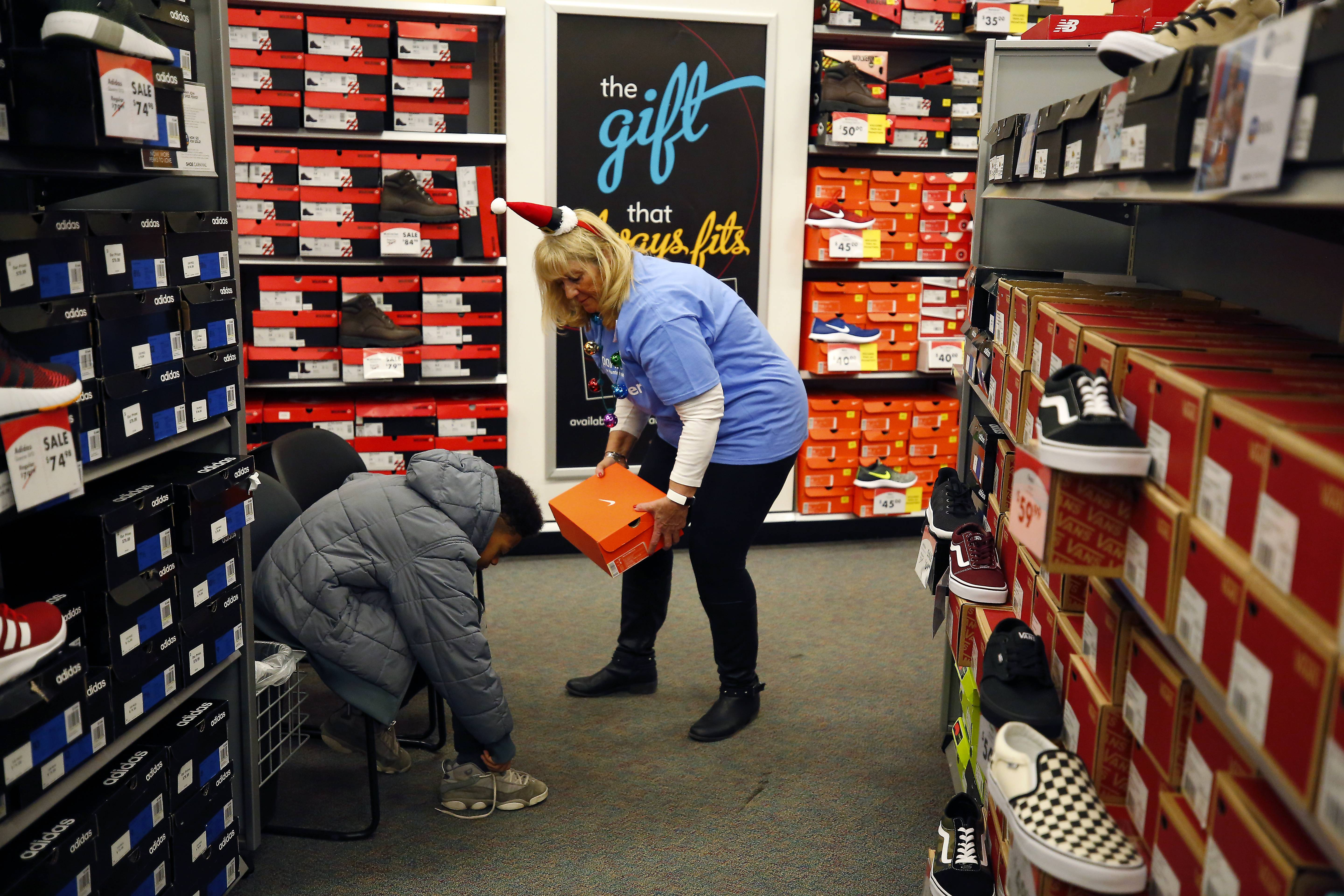 Jo Maniscalco of AT&T helps 11-year-old Darien Walls with a new pair of shoes Thursday at the Shoe Carnival in South Elgin. AT&T provided pairs of shoes to roughly 400 children in need from Elgin Area School District U-46 schools.