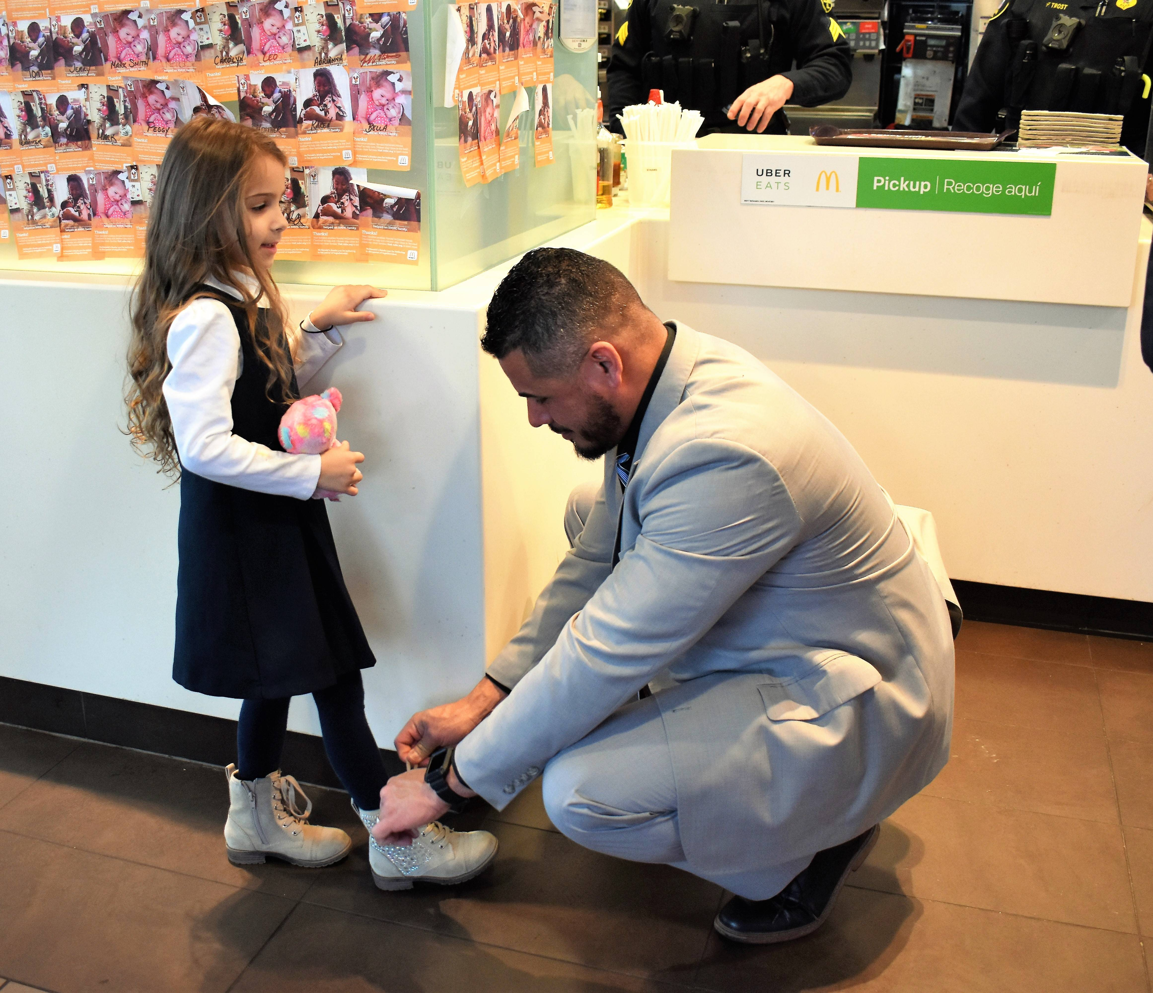 Miss Cassidy Aich is more than happy to let Elgin Police Sergeant Eric Echevarria tie her shoe for her.