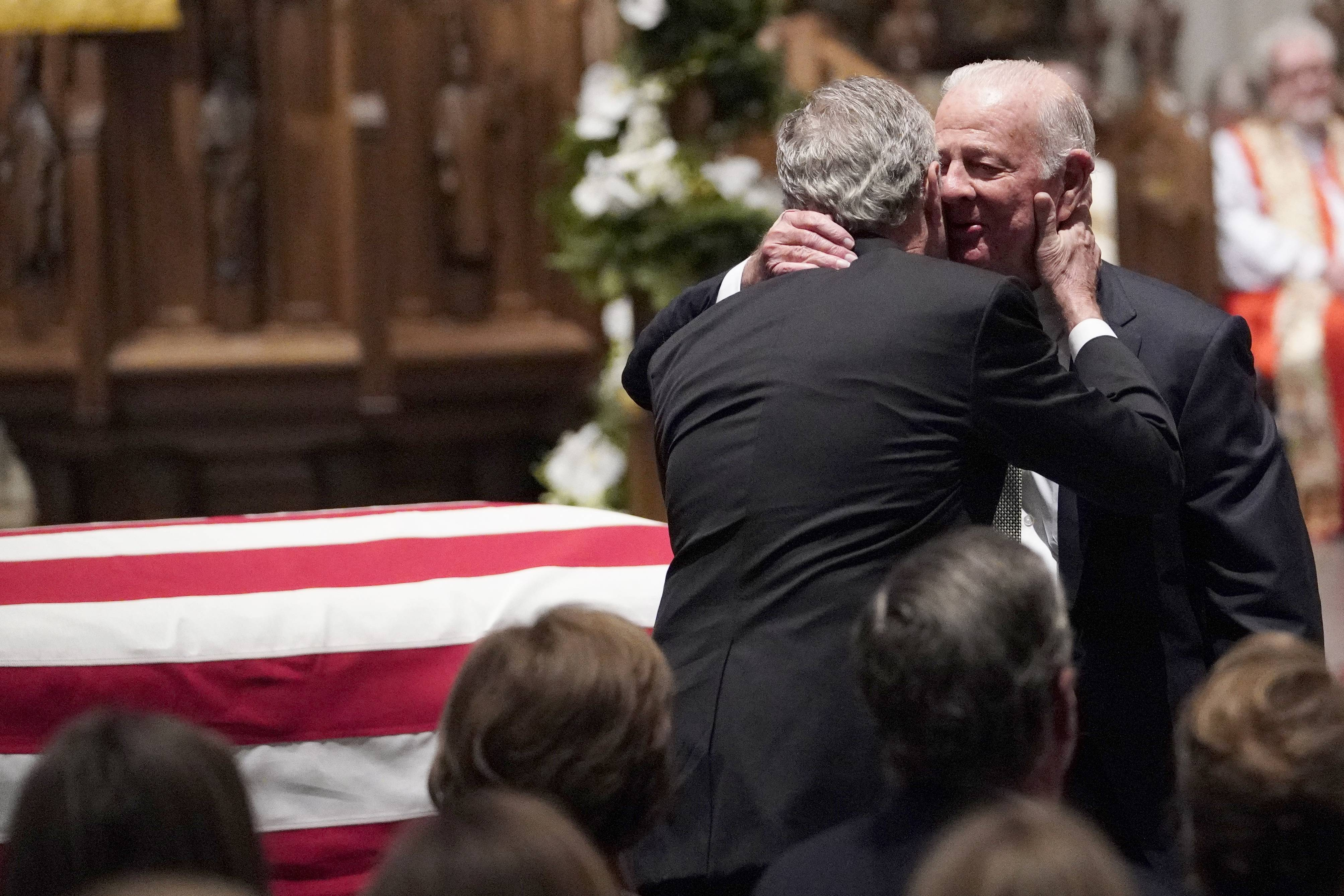Former President George W. Bush embraces former Secretary of State James Baker, right, Thursday after he gave a eulogy during the funeral for former President George H.W. Bush at St. Martin's Episcopal Church in Houston.