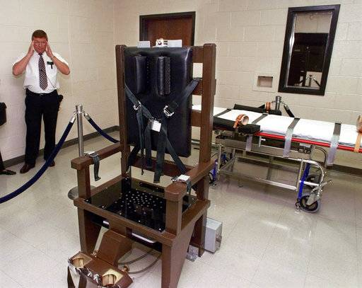 FILE - In this Oct. 13, 1999, file photo, Ricky Bell, then the warden at Riverbend Maximum Security Institution in Nashville, Tenn., gives a tour of the prison's execution chamber. David Earl Miller, a Tennessee death row inmate, was waiting Wednesday, Dec. 5, 2018, to see whether the U.S. Supreme Court or the governor would halt his Thursday execution in the electric chair.