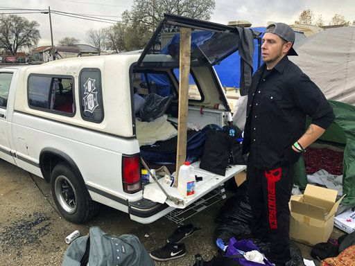 In this Tuesday, Dec. 4, 2018 photo Michael Jones organizes a pile of donated blankets, sleeping bags and clothes in a fairgrounds parking lot that's become home to some of the people displaced by California's deadliest wildfire in Chico, Calif. Jones lost nearly everything he owns when the fire destroyed his trailer and his mom's home in Paradise last month, but he's determined to stay put because he doesn't want to be a burden on his friends and relatives.