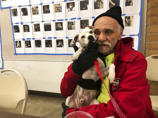 In this Tuesday, Dec. 4, 2018 photo, Bob Talk cuddles his dog, Princeton, at a Red Cross disaster shelter in Chico, Calif. Talk had lived in his trailer for three days when fire swept through the town of Paradise and destroyed his home last month, making him homeless again. The future is uncertain for all of the fire's victims, but it's uniquely challenging for the many like Talk who were already living on the edge, homeless or nearly so, before escaping with their lives and little else.