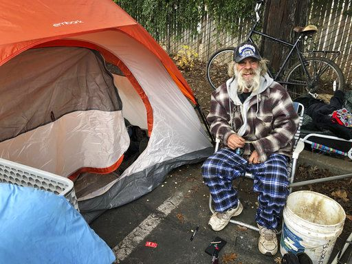 In this Tuesday, Dec. 4, 2018 photo, Steve Wilson poses for a photo next to the tent where he's been sleeping in the parking lot of an abandoned Toys R Us in Chico, Calif. Wilson, who was homeless in Chico before the worst wildfire in California history destroyed nearby Paradise, has seen the streets grow more crowded with homeless people.