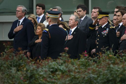 Jeb Bush, from left, his wife Columba Bush, former President George W. Bush and his wife Laura Bush, partly seen, stand for the national anthem before former President George H.W. Bush's internment close to his presidential library in College Station, Texas, Thursday, Dec. 6, 2018. (Smiley N. Pool/The Dallas Morning News via AP, Pool)