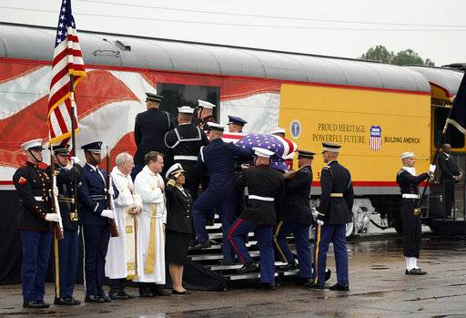 The flag-draped casket of former President George H.W. Bush is carried by a joint services military honor guard Thursday, Dec. 6, 2018, in Spring, Texas, as it is placed on a Union Pacific train.