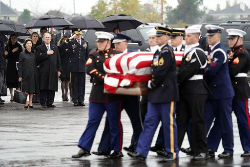 Former President George W. Bush and Laura Bush watch as the flag-draped casket of former President George H.W. Bush is carried by a joint services military honor guard Thursday, Dec. 6, 2018, in Spring, Texas, to a Union Pacific train.