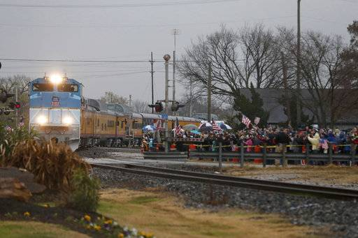 People pay their respects as the train carrying the casket of former President George H.W. Bush passes through Navasota, Texas Thursday, Dec. 6, 2018.