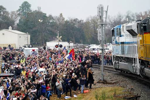 People pay their respects as the train carrying the casket of former President George H.W. Bush passes Thursday, Dec. 6, 2018, along the route from Spring to College Station, Texas.