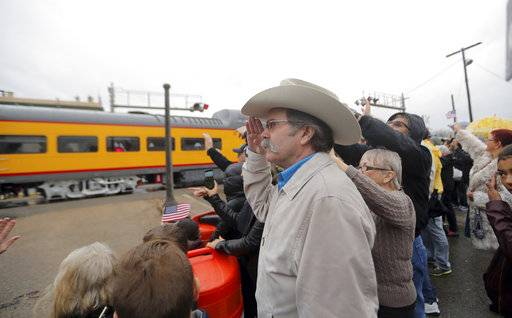 Dennis Ivy from Huntsville, Texas, left, salutes as people pay their respects as the train carrying the casket of former President George H.W. Bush passes through Navasota, Texas Thursday, Dec. 6, 2018.
