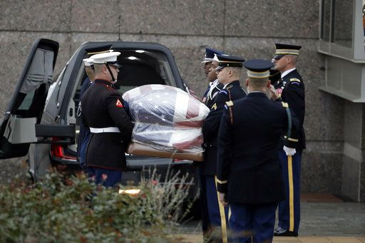 The flag-draped casket of former President George H.W. Bush is carried by a joint services military honor guard outside the George H.W. Bush Presidential Library and Museum Thursday, Dec. 6, 2018, in College Station, Texas.