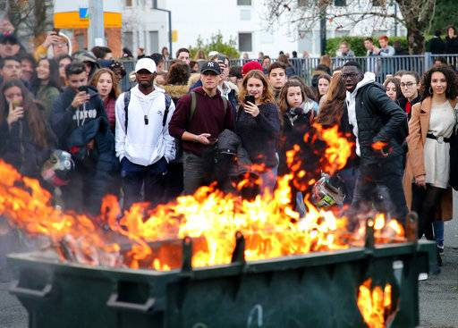 Students watch a burning trash bin outside their school in Bayonne, southwestern France, Thursday, Dec.6, 2018. Protesting students are disrupting schools and universities Thursday, and drivers are still blocking roads around France, now demanding broader tax cuts and government aid.