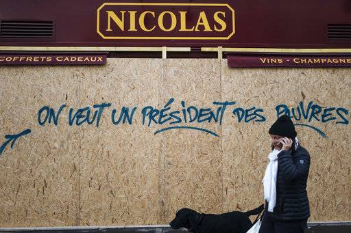 FILE - In this Sunday, Dec. 2, 2018 file picture, a woman walks past a graffiti on a boarded up wine shop reading 'We want a president for the poor', near the Arc de Triomphe, in Paris, France. One year and a half after he came into power, Macron is facing violent protests over rising taxes.