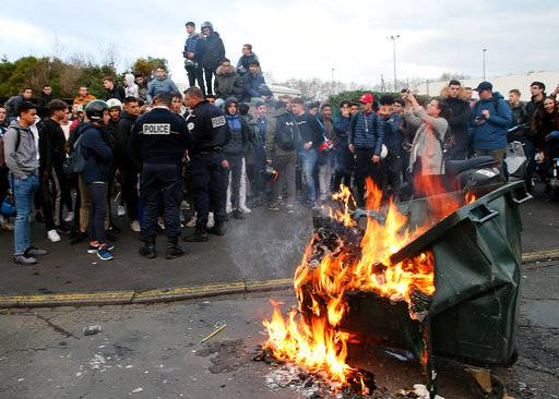 Students talk to police officers by a burning trash bin outside their school in Bayonne, southwestern France, Thursday, Dec.6, 2018. Protesting students are disrupting schools and universities Thursday, and drivers are still blocking roads around France, now demanding broader tax cuts and government aid.