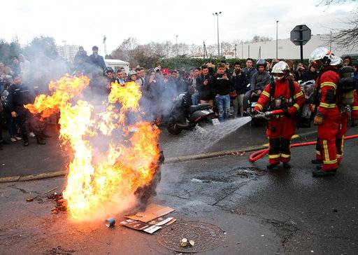 Friefighters turn off fire on a burning trash bin outside a school in Bayonne, southwestern France, Thursday, Dec.6, 2018. Protesting students are disrupting schools and universities Thursday, and drivers are still blocking roads around France, now demanding broader tax cuts and government aid.