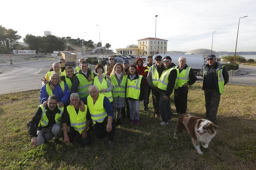 A group of demonstrators wearing their yellow vest pose on an occupied traffic circle, Wednesday, Dec. 5, 2018 outside La Mede oil refinery, near Martigues, southeastern France. Trade unions and farmers pledged Wednesday to join nationwide protests against President Emmanuel Macron, as concessions by the government failed to stem the momentum of the most violent demonstrations France has seen in decades.