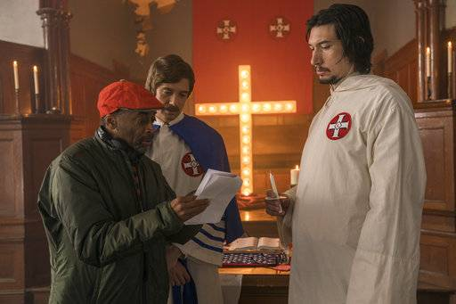 "This image released by Focus Features shows director Spike Lee, left, with actors Topher Grace, center, and Adam Driver on the set of Lee's film ""BlacKkKlansman."" On Thursday, Dec. 6, 2018, Lee was nominated for a Golden Globe award for best director for the film. The 76th Golden Globe Awards will be held on Sunday, Jan. 6. (David Lee/Focus Features via AP)"