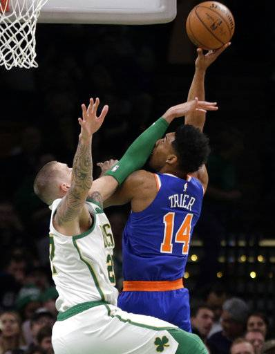 New York Knicks guard Allonzo Trier (14) tries to shoot over Boston Celtics forward Daniel Theis (27) during the first quarter of an NBA basketball game Thursday, Dec. 6, 2018, in Boston.