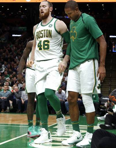 Boston Celtics center Aron Baynes (46) limps off the court with an injury as teammate Al Horford, right, walks with him in the first quarter of an NBA basketball game against the New York Knicks, Thursday, Dec. 6, 2018, in Boston.