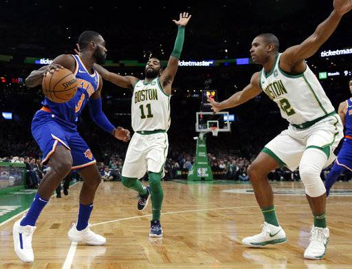 New York Knicks guard Tim Hardaway Jr. (3) looks for room to move against the defense of Boston Celtics guard Kyrie Irving (11) and center Al Horford (42) during the second half of an NBA basketball game Thursday, Dec. 6, 2018, in Boston. The Celtics won 128-100.