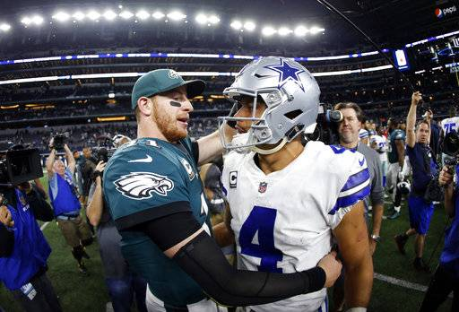 FILE - In this Nov. 19, 2017, file photo, Philadelphia Eagles' Carson Wentz, left, and Dallas Cowboys' Dak Prescott, right, greet each other after their NFL football game, in Arlington, Texas. Prescott and the Cowboys saved their season with a win in Philadelphia a month ago. Now Carson Wentz and the defending champion Eagles are trying to do the same in Texas against first-place Dallas on Sunday.