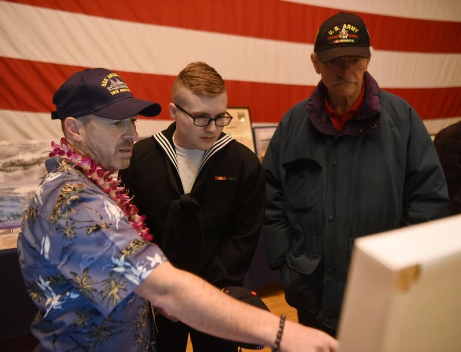 Photographer Paolo Cascio, left, shows photos and artifacts to seamen Drew Lloyd, middle, and veteran Don Castella after a Pearl Harbor commemoration ceremony at Great Lakes Naval Station.