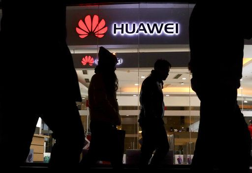 Pedestrians walk past a Huawei retail shop in Beijing Thursday, Dec. 6, 2018. China on Thursday demanded Canada release a Huawei Technologies executive who was arrested in a case that adds to technology tensions with Washington and threatens to complicate trade talks.
