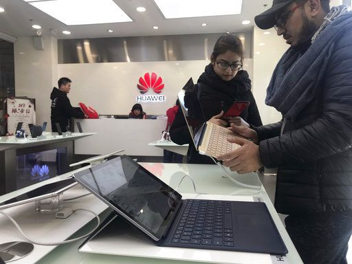Foreigners look at a Huawei computer at a Huawei store in Beijing, China, Thursday, Dec. 6, 2018. Canadian authorities said Wednesday that they have arrested the chief financial officer of China's Huawei Technologies for possible extradition to the United States.