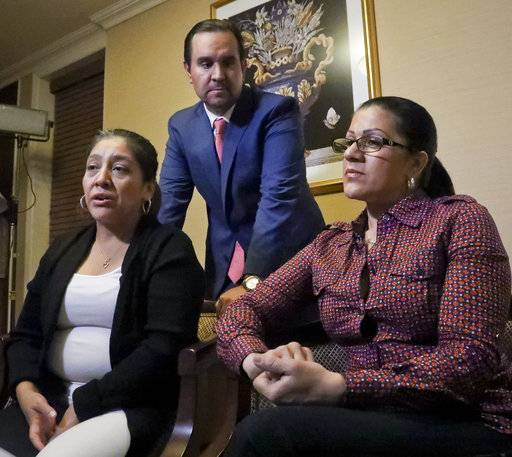 Attorney Anibal Romero, center, joins his clients Victorina Morales, left, and Sandra Diaz, right, during an interview, Friday Dec. 7, 2018, in New York. Morales and Diaz, who recalled their experience working at President Donald Trump's golf resort in Bedminster, N.J., say they used false legal documents to get hired and supervisors knew it.