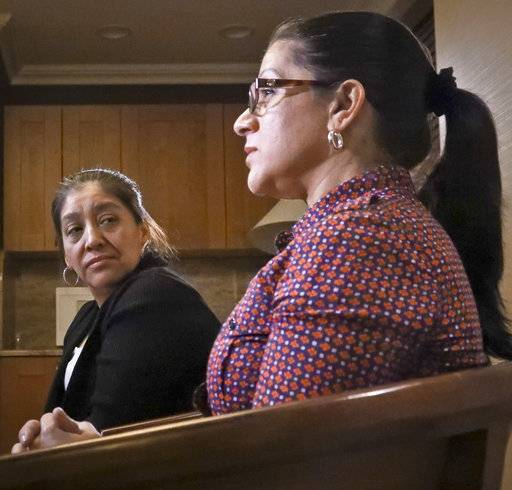 Victorina Morales, left, listens as Sandra Diaz, right, recall her experience working at President Donald Trump's golf resort in Bedminster, N.J., during an interview, Friday Dec. 7, 2018, in New York. Both Morales and Diaz say they used false legal documents to get hired at the resort and supervisors knew it.