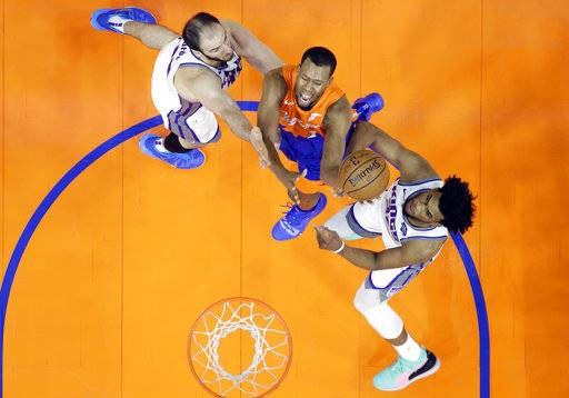 Cleveland Cavaliers' Rodney Hood, center, drives to the basket between Sacramento Kings' Kosta Koufos, left, and Sacramento Kings' Marvin Bagley III in the first half of an NBA basketball game, Friday, Dec. 7, 2018, in Cleveland.