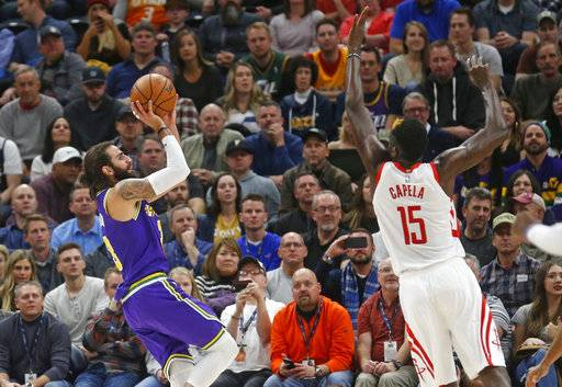 Utah Jazz guard Ricky Rubio (3) shoots as Houston Rockets center Clint Capela (15) defends during the first half during an NBA basketball game Thursday Dec. 6, 2018, in Salt Lake City.