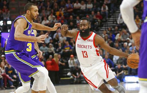 Houston Rockets guard James Harden (13) drives around Utah Jazz center Rudy Gobert, left, during the first half of an NBA basketball game Thursday Dec. 6, 2018, in Salt Lake City.