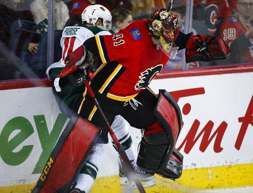 Minnesota Wild's Zach Parise, left, is checked by Calgary Flames goalie Mike Smith during second-period NHL hockey game action in Calgary, Alberta, Thursday, Dec. 6, 2018. (Jeff McIntosh/The Canadian Press via AP)