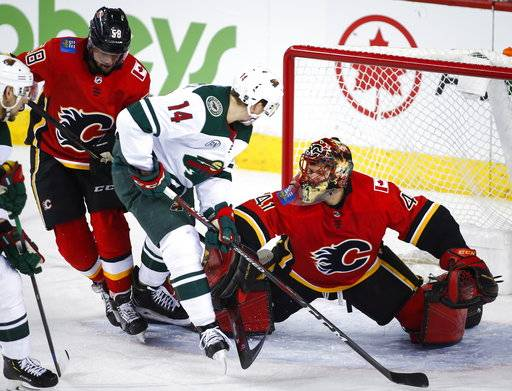 Minnesota Wild's Joel Eriksson, center, of Sweden, is shoved away from the net by Calgary Flames goalie Mike Smith, right, as Flames' Oliver Kylington, of Sweden, looks on during first-period NHL hockey game action in Calgary, Alberta, Thursday, Dec. 6, 2018. (Jeff McIntosh/The Canadian Press via AP)