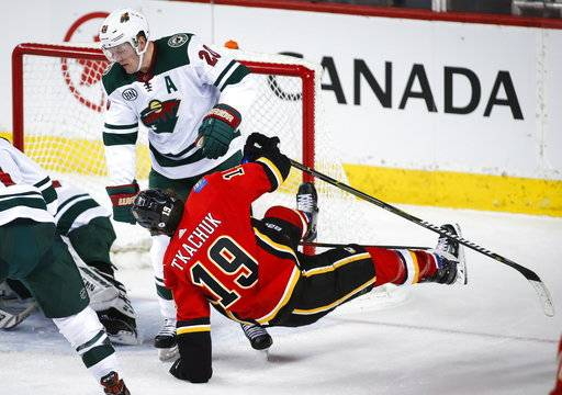 Minnesota Wild's Ryan Suter, left, sends Calgary Flames' Matthew Tkachuk to the ice during second-period NHL hockey game action in Calgary, Alberta, Thursday, Dec. 6, 2018. (Jeff McIntosh/The Canadian Press via AP)