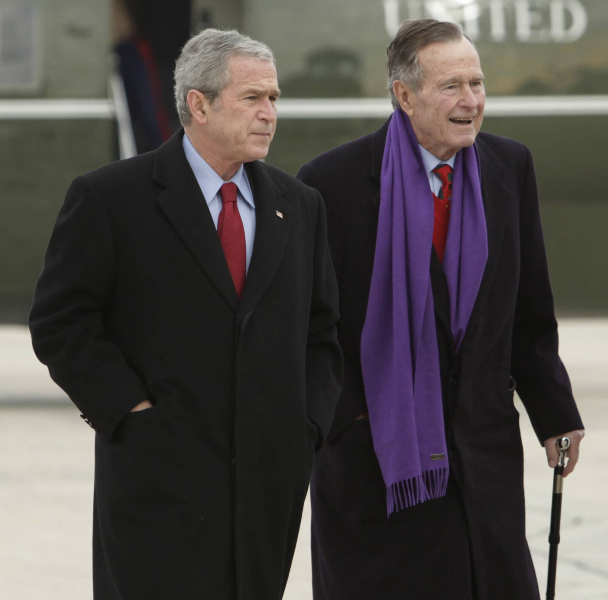 Former Presidents George W. Bush, left, and George H.W. Bush walk together in 2008 at Andrews Air Force Base in Maryland.